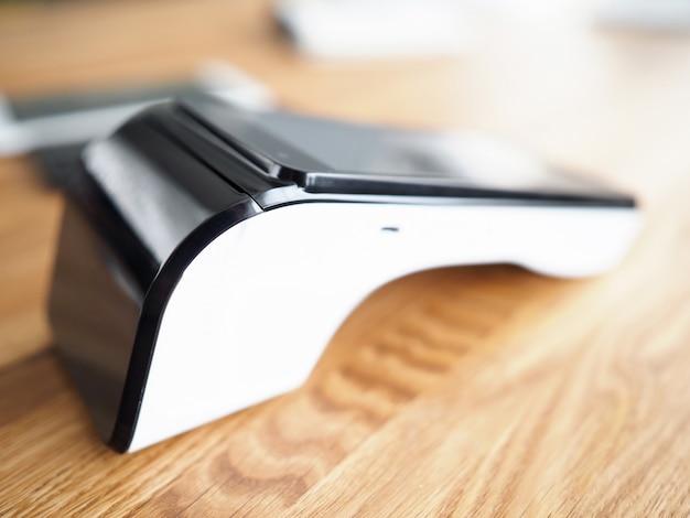 木製の表面に銀行のpos端子があります。携帯端末。オンラインバンキングによるサービスの支払い。銀行カード取得。支払い情報とシステム設定はオンラインで利用できます