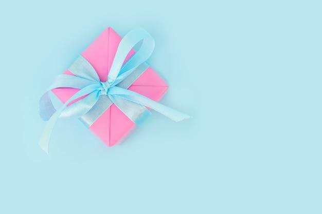 テキストのための場所とピンクの紙onblueのクリスマスプレゼント。