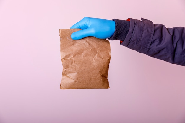 Ð¡oncept of safe home delivery in a pandemic. coronavirus 2019-ncov covid-19 protection. courier with paper bag hand in medical glove. copy space for text. stay at home online shopping concept.
