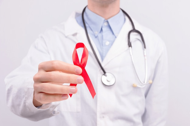 Oncological disease concept. doctor wearing white coat and stethoscope holding red ribbon as a symbol of aids.