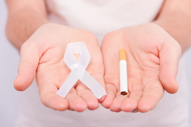 Oncological disease concept. man in white t-shirt holding white ribbon as a symbol of lung cancer in one hand and a cigarette in another.
