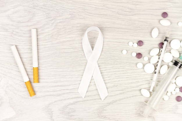 Oncological disease concept. white ribbon as a symbol of lung cancer, two cigarettes, pills and syringes isolated on light wooden table