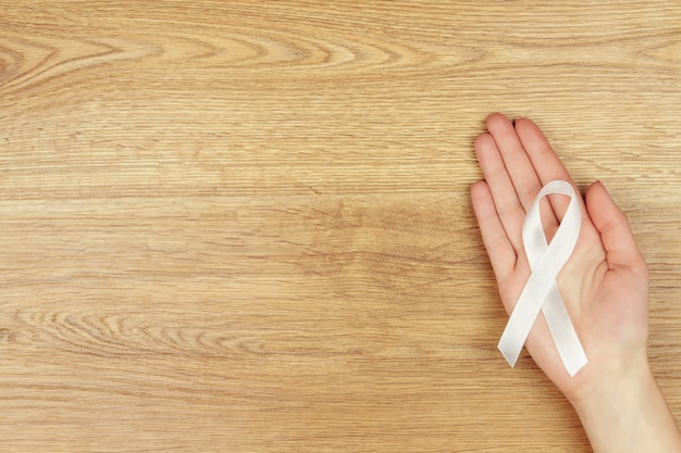 Oncological disease concept. woman's hand with a white ribbon as a symbol of lung cancer isolated on wooden background.