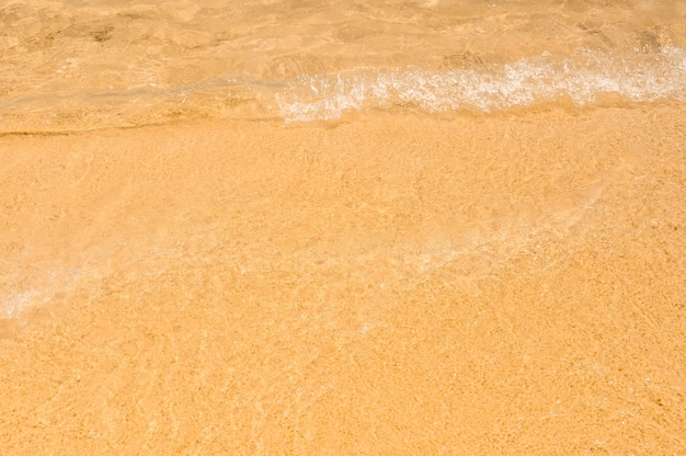 迫り来るソフトウェーブ。ビーチの海の水の抽象的な背景の下でビーチの細かい黄色の砂