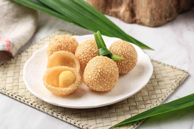 白い皿に盛り付けられたオンデオンドセサミシードボールは、中国の影響を受けたインドネシアのスナックをクローズアップ