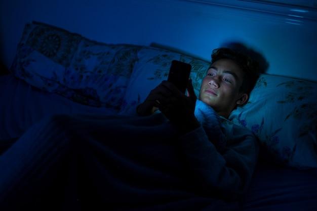 Один зависимый подросток у телефона использует его поздно ночью в своей спальне под одеялом в своей кровати - концепция и образ жизни, связанные с социальными сетями и сетями.