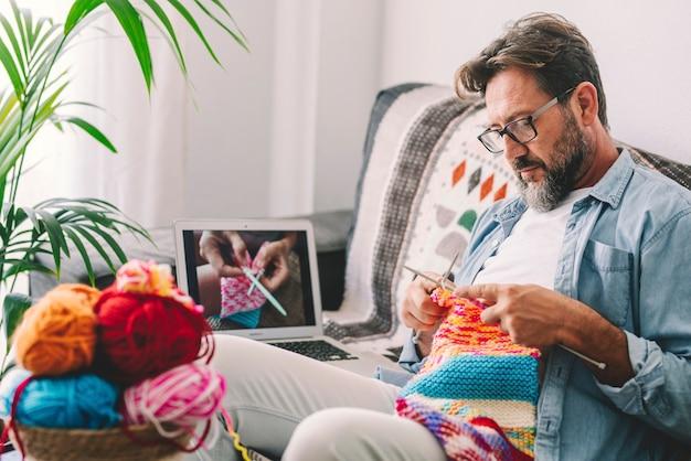 Один взрослый мужчина дома следит за онлайн-уроком по вязанию, чтобы расслабиться и насладиться отдыхом дома, сидя на диване - мужчины, вяжущие с помощью компьютерного класса - люди изнутри, образ жизни, хобби