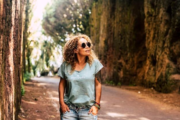 一人の大人のきれいな女性が、屋外の自然公園のレジャー活動を楽しんでいる森の木の風光明媚な道路の場所を一人で歩きます-人々と自然の背景