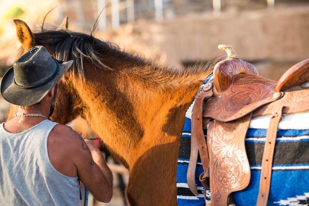 Один взрослый ухаживает за лошадью или готовит ее к гонке в одиночку на ранчо - здоровая и подтянутая лошадь.