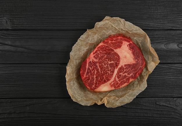 검은색 테이블 배경 위에 포장된 갈색 종이 양피지 위에 1세 마블링된 생 ribeye 쇠고기 스테이크