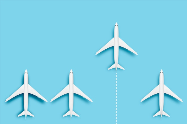 One airplane is faster than several others on a blue background. concept travel, airline tickets, flight, route pallet, transfer, leader, boss, creative.