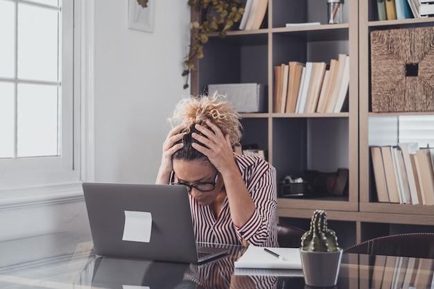 집에 혼자 있는 불행하고 슬픈 여성 한 명이 노트북을 사용하고 머리에 손을 얹고 그것을 보고 있습니다. 문제 해결에 어려움을 겪는 여성