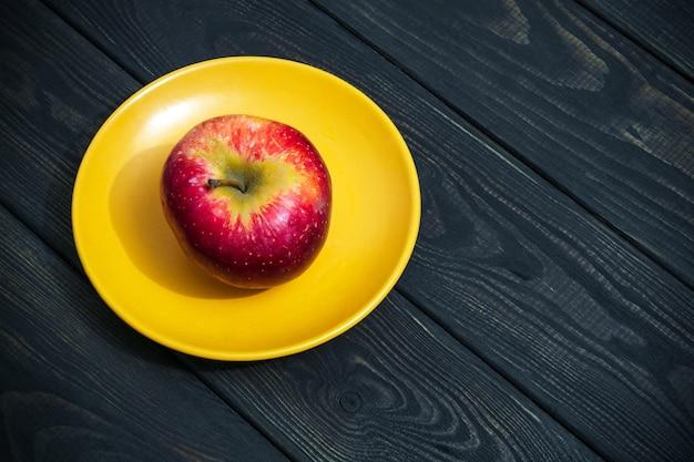 주황색 접시에 한 사과