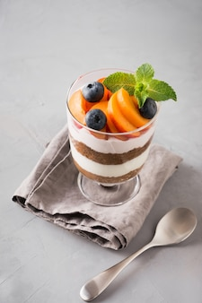 One apricot trifle, chocolate biscuit, layered dessert with fresh berry and gentle cream cheese