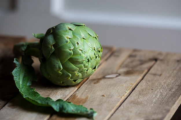 One artichoke on a wooden rustic surface, copy space