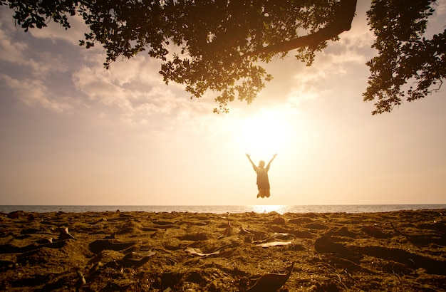 One asian girl jumping on the beach at the sunset time