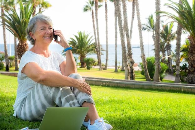 Одна привлекательная старшая женщина, сидящая на лужайке с ноутбуком, используя мобильный телефон