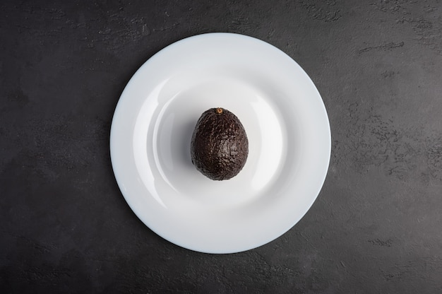 One avocado in the peel served in white plate on moody black background. top view, healthy diet concept, copy space