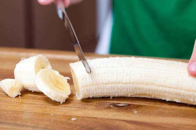 One banana is sliced on a food slicing board, yellow fresh banana during slicing