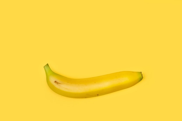 One banana on a yellow background with copy space
