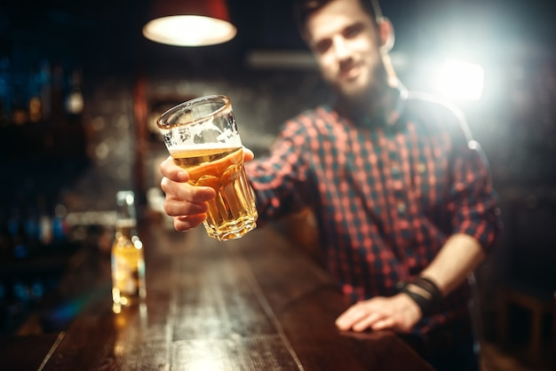 One bearded man holds glass of beer, guy at the bar counter. male person leisure in pub