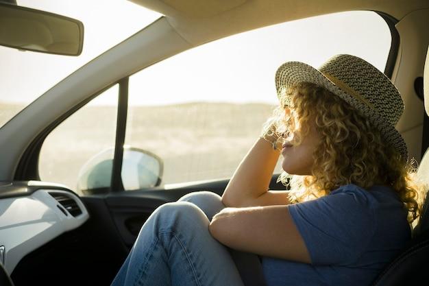 Одна красивая кудрявая женщина наслаждается отдыхом на открытом воздухе, путешествуя на машине