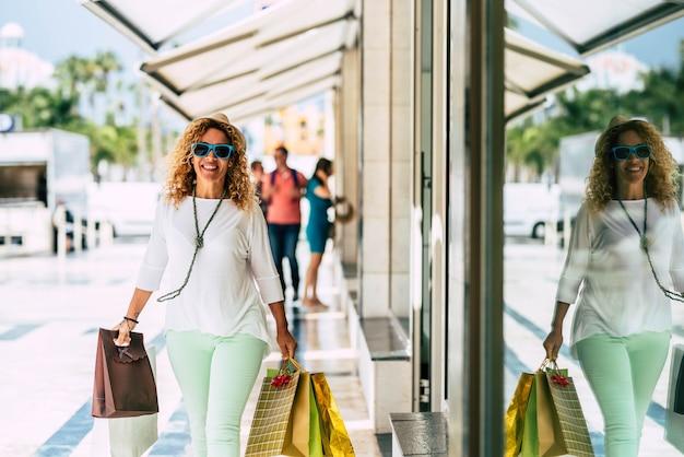 많은 쇼핑백을 손에 들고 쇼핑몰을 걷고 있는 한 아름다운 곱슬머리 여성이 웃고 카메라를 바라보고 있습니다 - 쇼핑중독 개념과 선물을 하거나 선물을 사는 것
