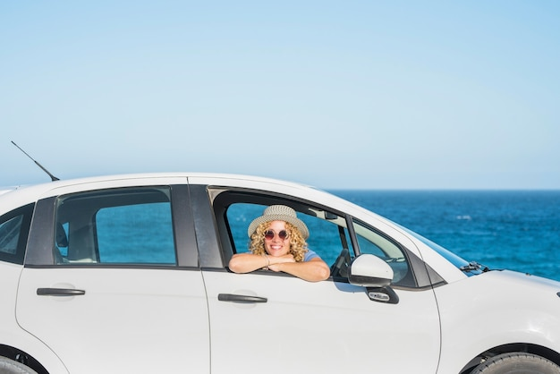 Одна красивая счастливая женщина смотрит в камеру изнутри машины с морем или океаном на месте происшествия