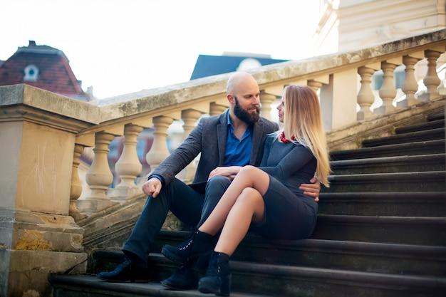 Одна красивая стильная пара молодой женщины и старшего мужчины с длинной черной бородой, сидящей, обнимая близко друг к другу на улице в осенней улице на лестнице солнечный день, горизонтальное изображение