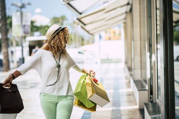 쇼핑몰에서 혼자 쇼핑을 하는 쇼핑백을 든 아름다운 여성 - 옷 등에 돈을 쓰는 부유한 성인