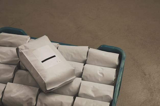 Un grande pacchetto vuoto sigillato con il prodotto presentato sopra una scatola di plastica con altri pacchetti.