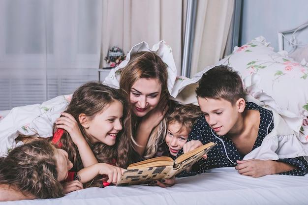 하나의 큰 행복한 가족. 엄마는 잠들기 전에 침대에서 아이들에게 책을 읽어줍니다.