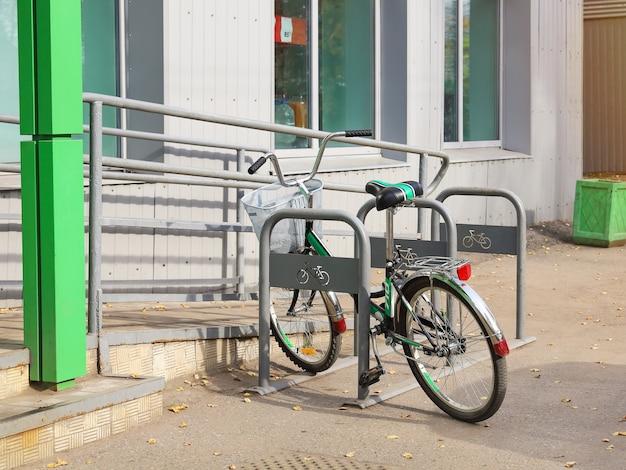 Один велосипед стоит на стоянке рядом с пандусом для передвижения людей с ограниченными возможностями.