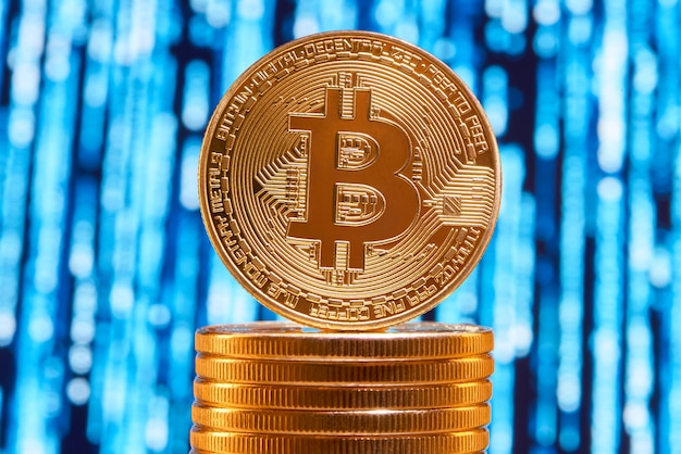 One bitcoin on edge placed on stack of golden bitcoins with blurred blue circuit on background.
