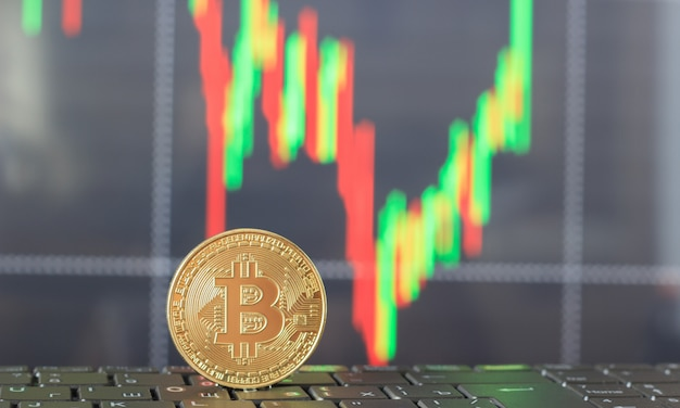 One bitcoin on the keyboard and a graph of the growth and fall in prices