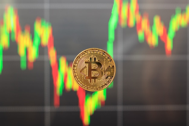 One bitcoin with a blurred graph in the background, the concept of rising and falling prices