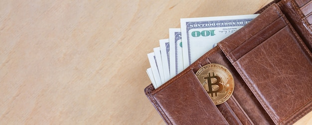 One bitcoin with dollar bills in brown leather wallet. virtual cryptocurrency trading and investment concept