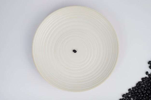 白い背景の上のプレートに1つの黒豆。上面図。