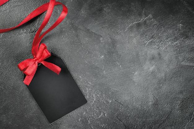 灰色のコンクリートの背景に赤い弓と1つの黒いラベル