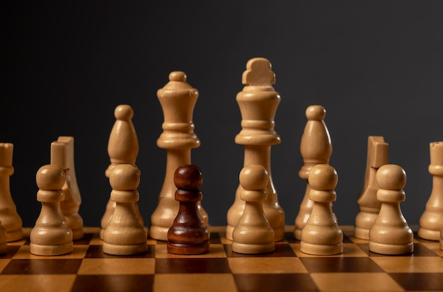 One black pawn unique and different in group of other chess pieces. concept of diversity and uniqueness.