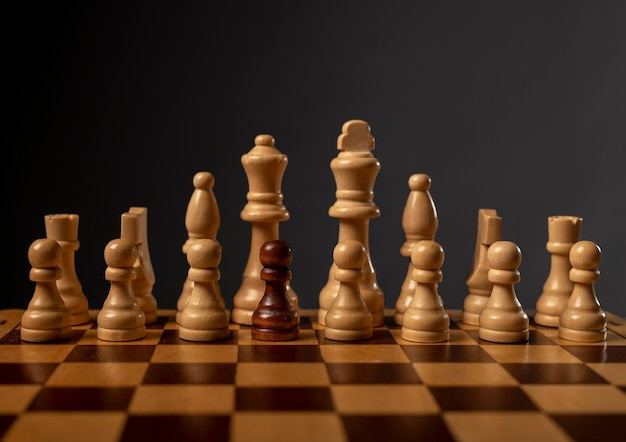 One black pawn unique and different in group of other chess pieces. concept of diversity.