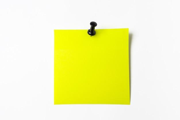 Один пустой квадрат желтый липкий лист бумаги с кнопкой на белом фоне. напоминаю вам информацию. место для текста.