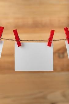 ロープ ストリング ペグに洗濯はさみでぶら下がっている 1 つの空白の白いメモ カード。縦枠。