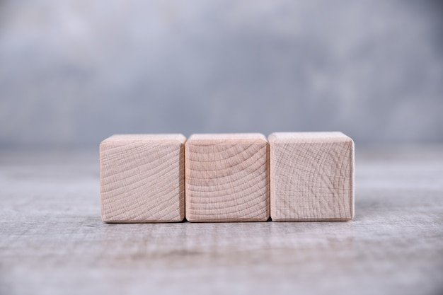 One blank wooden cube on the table.