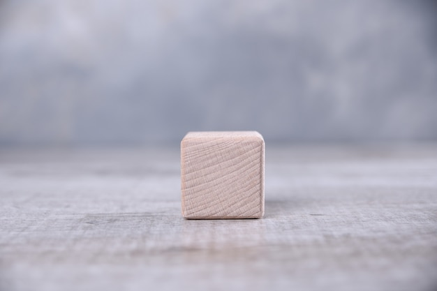 One blank wooden cube with space for your word, letter, symbol on the table. place for text, free copy space