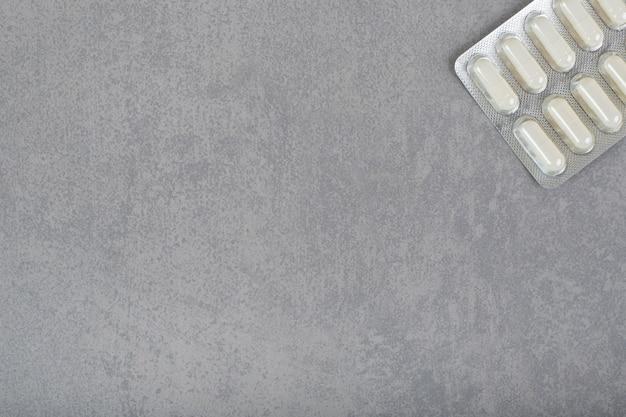 회색 표면에 흰색 알약이 있는 물집 1개