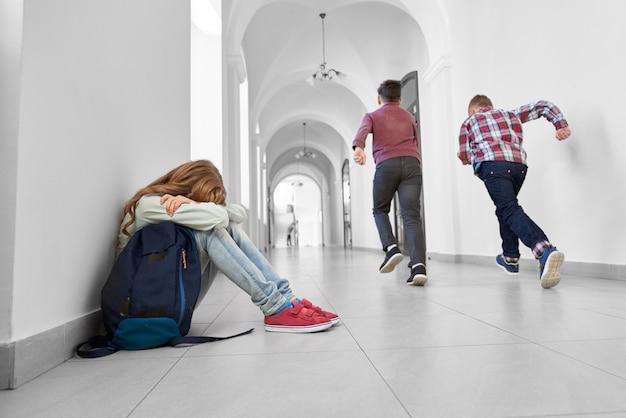 학교에서 바닥에 앉아 울고 한 금발 소녀