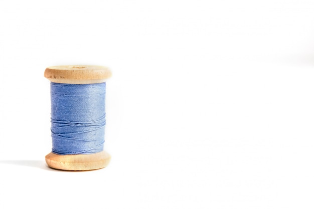 One blue thread bobbin isolated on white background