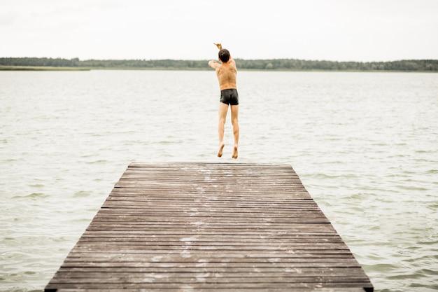 木製の橋から水に飛び込む一人の少年、背面図、夏の時間、休暇