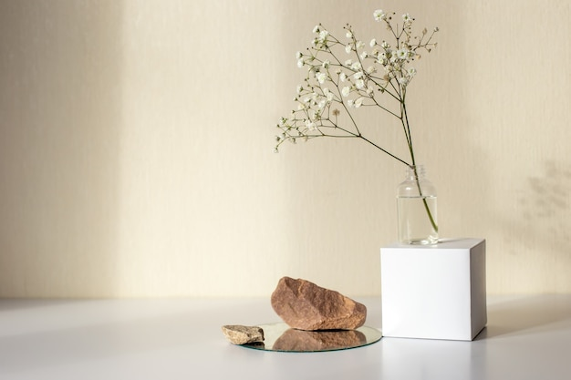 One branch of a white gypsophila flower standing on a white paper cube and stones